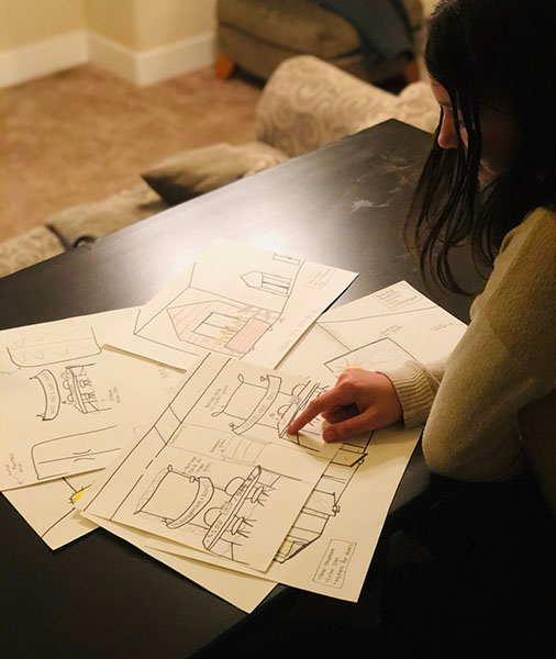 Production set design student, sitting at desk, reviewing design sketches.