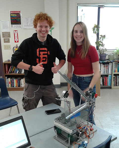 Two engineering students, posing for the camera with their robotics project.