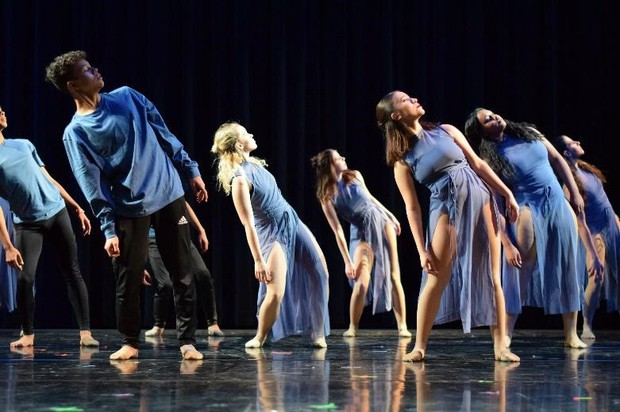 Image of inspire contemporary dancers from the fall gala. In blue outfits with black backdrop.
