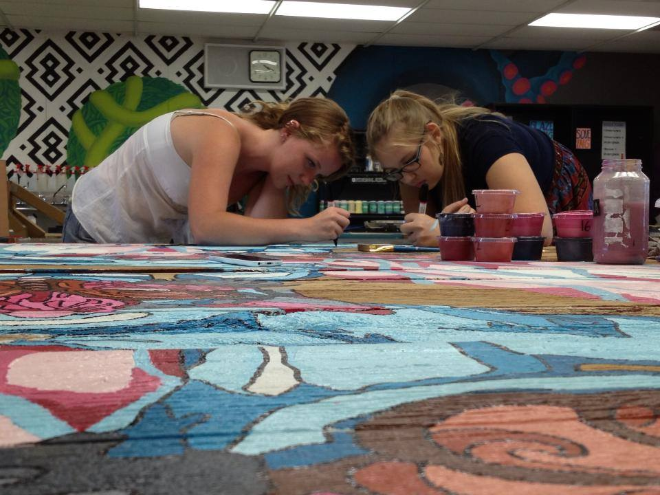 Two students hovering over large collaborative painting