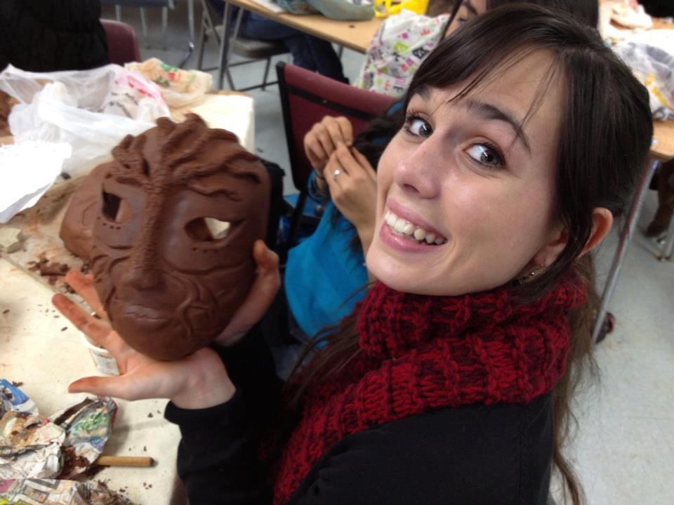 Inspire student posing for camera with ceramic creation
