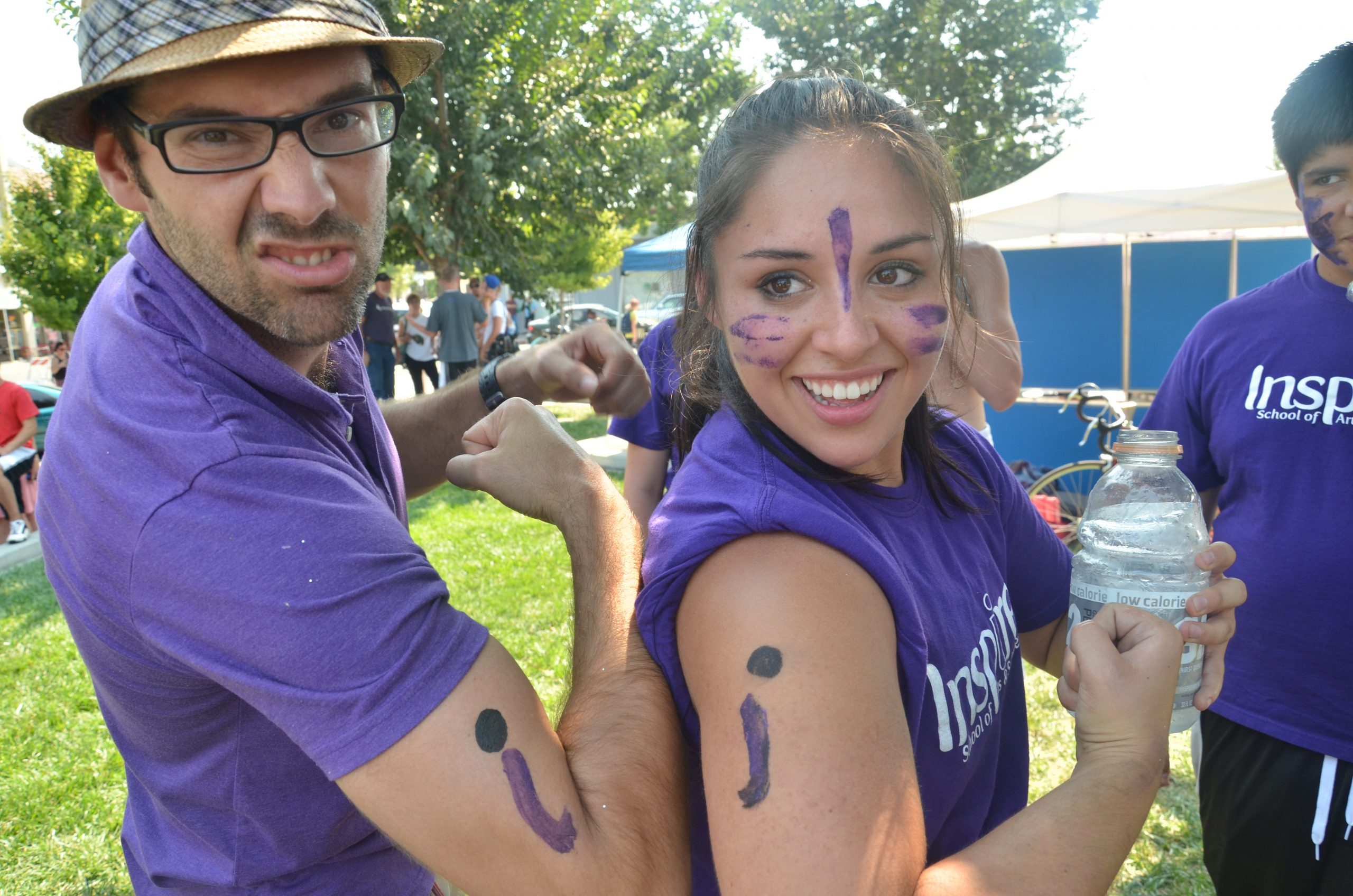 Teacher and student flexing with an i painted on their arm