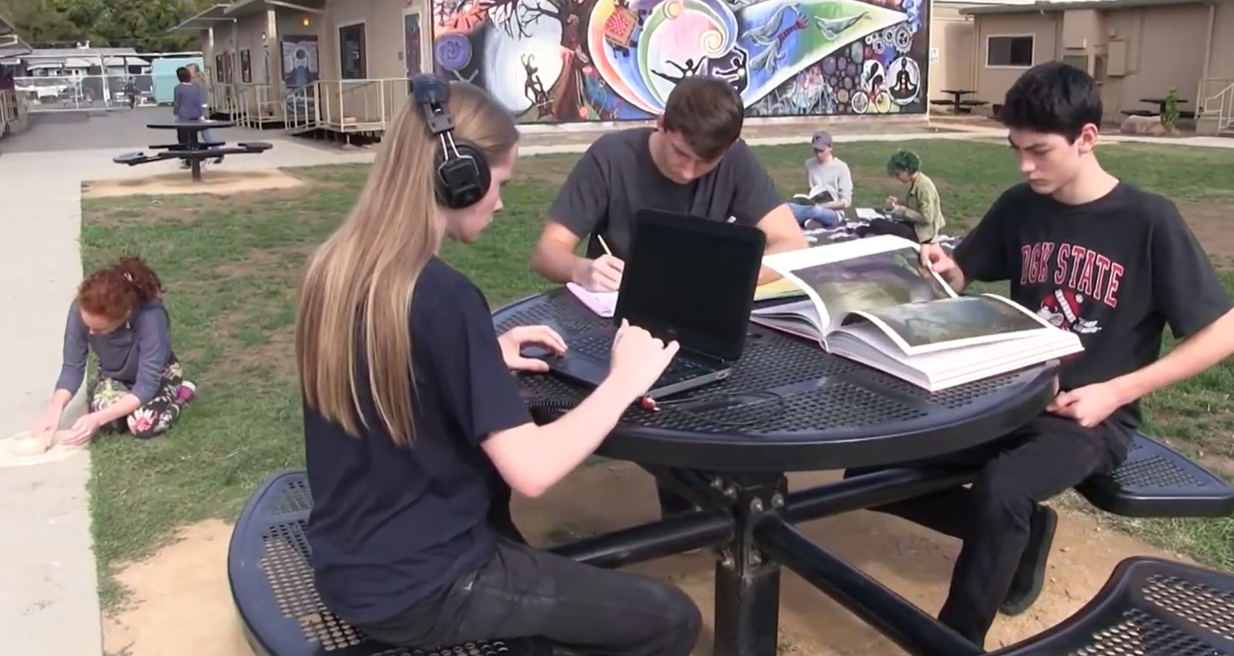 Student working on a computer with earphones on