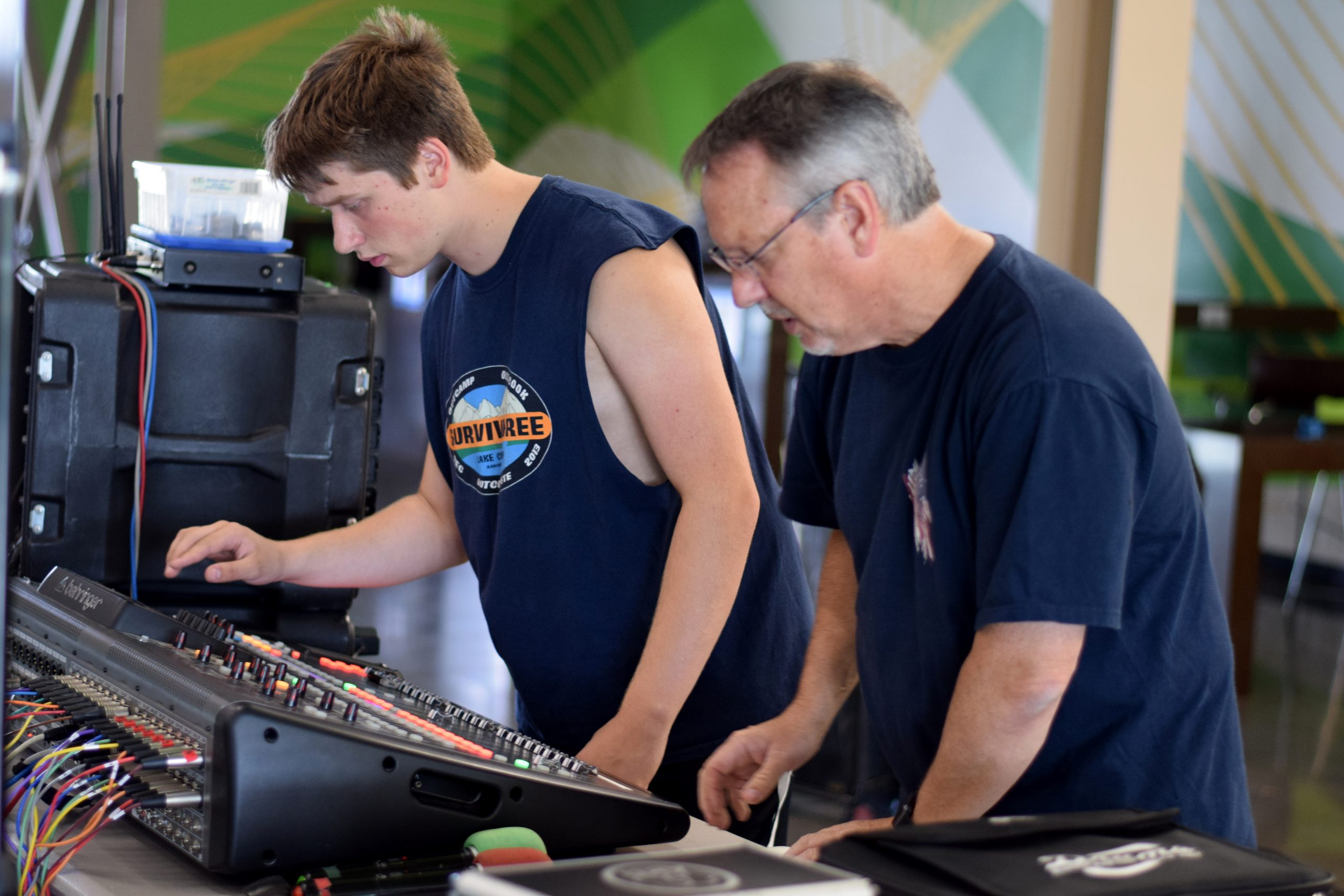 Image of recording arts student with advisor, Jim White, working on sound board together
